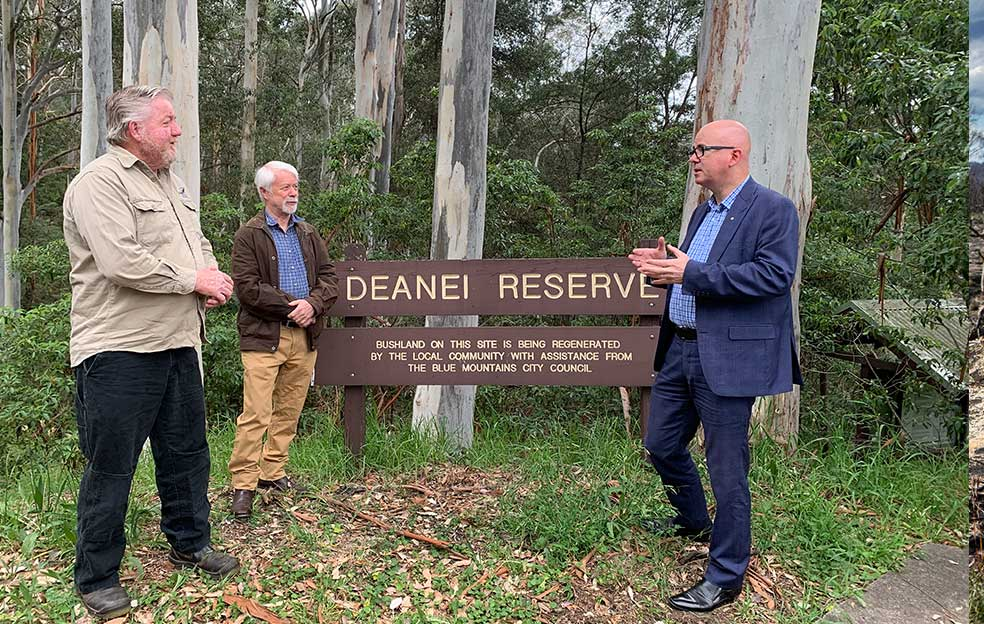 Councillor, staff member and Mayor in front of nature reserve